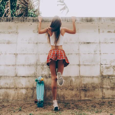Jeune femme sportive avec dans une mini-jupe tartan rouge avec skateboard penny bleu essayant de grimper par-dessus la clôture d'un jardin tropical. Photo de style de vie en plein air par une journée d'été ensoleillée.