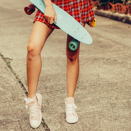 Gros plan sur une femme sportive vêtue d'une mini-jupe en tartan rouge tient son shortboard de skateboard bleu penny tout en se tenant dans la rue tropicale. Photo de style de vie en plein air par une journée d'été ensoleillée. Banque d'images