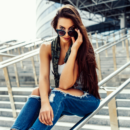Happy beautiful girl with long healthy hair in casual clothes sitting on railing, touch her trendy fashion sunglasses and have fun. Young sexy lady enjoying summer day near business or sport building. Stock Photo