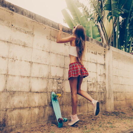 Sporty young woman with in a red tartan mini skirt with blue penny skateboard trying to climb over the fence of a tropical garden. Outdoor lifestyle picture on a sunny summer day.