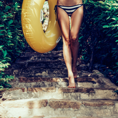 Close up of a sporty young woman in striped bikini and white t-shirt with yellow inflatable swimming ring walking on stone steps in a tropical garden. Outdoor lifestyle picture on a sunny summer day.