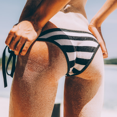 Sandy butt of a young beautiful sporty woman in sexy striped black and white bikini panties on the tropical sea shore background. Outdoor lifestyle picture on a hot sunny summer day. Banco de Imagens