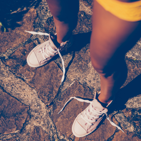 Beautiful athletic young girl in a yellow knitted bikini looks at her sneakers with unleashed shoelaces on the stone path in a tropical garden. Outdoor lifestyle on a hot sunny summer day. Banco de Imagens