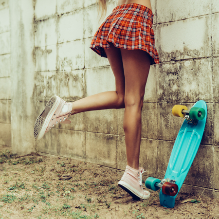Close up of a young girl with sporty in a red tartan mini skirt with blue penny skateboard trying to climb over the fence of a tropical garden. Outdoor lifestyle picture on a sunny summer day.
