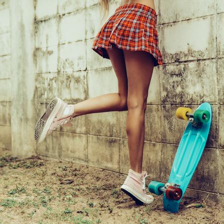 Primo piano di una giovane ragazza sportiva in una minigonna scozzese rossa con skateboard penny blu che cerca di scavalcare la recinzione di un giardino tropicale. Foto di stile di vita all'aperto in una giornata di sole estivo.
