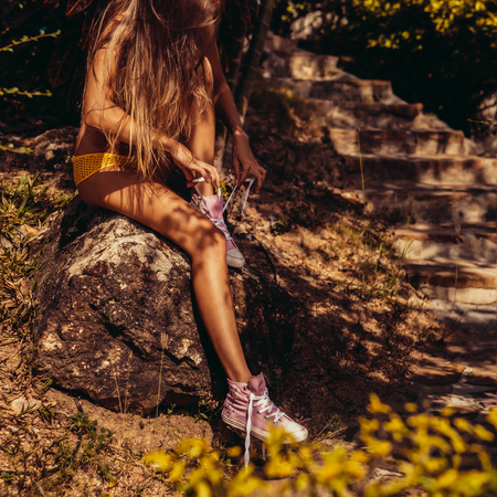 Skinny sexy young woman in a yellow swimsuit tying shoelaces in her pink sneakers while sitting on a stone near steps in a tropical garden. Outdoor lifestyle picture on a sunny summer day. Banco de Imagens