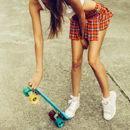 Skinny young lady in a red tartan mini skirt and sunglasses hold her blue penny skateboard shortboard while stands on the tropical street. Outdoor lifestyle picture on a sunny summer day.
