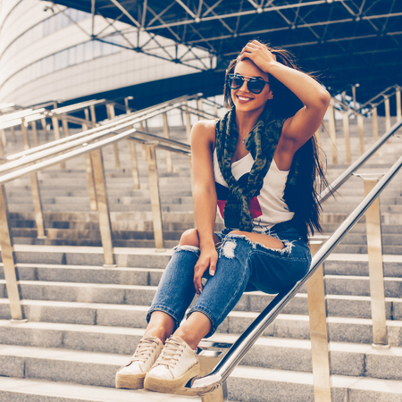 Happy beautiful girl in trendy fashion sunglasses and casual clothes sitting on railing, touch her long healthy hair and have fun. Young sexy lady enjoying summer day near business or sport building. Stock Photo