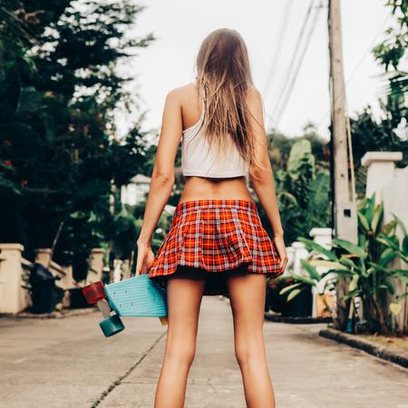 Une jeune femme maigre avec une coupe courte en tartan rouge avec un shortboard de skateboard bleu penny se dresse dans la rue tropicale. Photo de style de vie en plein air par une journée d'été ensoleillée.