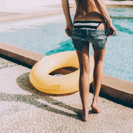 Sexy young lady with athletic butt in a striped bikini with yellow inflatable swimming ring takes off her jeans shorts at the refreshing pool. Outdoor lifestyle picture on a sunny summer day.