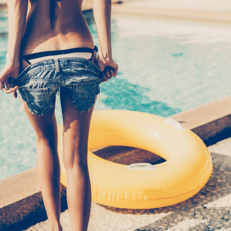 Sporty young woman with sexy athletic butt in a striped bikini with yellow inflatable swimming ring takes off her jeans shorts at the refreshing pool. Outdoor lifestyle picture on a sunny summer day.