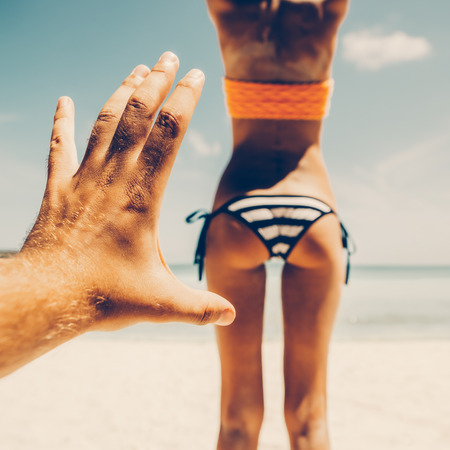 Mans hand trying to touch tanned fit butt of a sporty young beautiful female in a sexy stripped bikini on a sea shore background. Outdoor lifestyle picture on a hot sunny summer day.