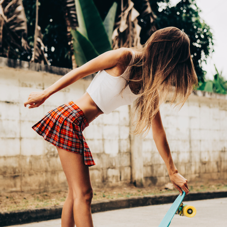 Skinny young woman with sporty butt in a sexy red tartan mini skirt with blue penny skateboard shortboard stands on the tropical street. Outdoor lifestyle picture on a sunny summer day.