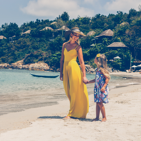 Beautiful blonde woman in long yellow tunic dress with her pretty little girl in floral dress walking at seaside. They holding hands look to each other. Happy family on the beach. Happy mothers day.