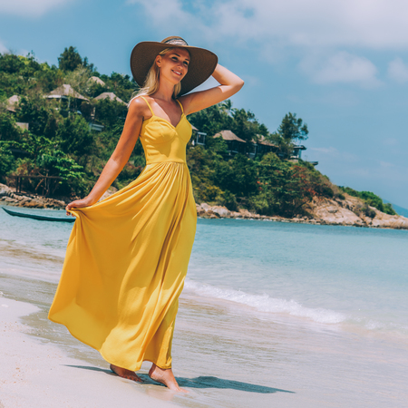 Carefree beautiful elegant blonde girl in beach straw hat holding her long yellow dress and walking barefoot by sand of tropical shore. Natural woman beauty. Lady looking to the beach and smiles.