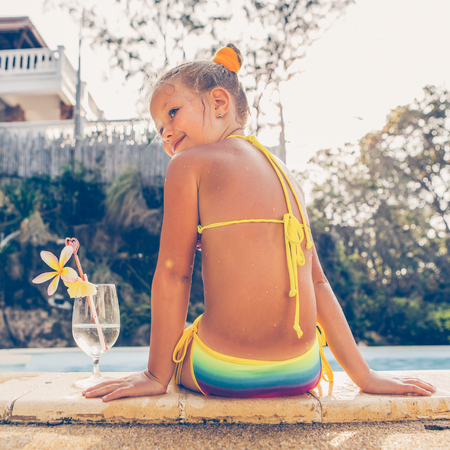 Cute little blonde girl swimming in big pool. Big glass with water, straw and frangipani stay on the pool edge. Little lady sit on the edge of the pool. Sunbathing and leisure on sunny summer day.