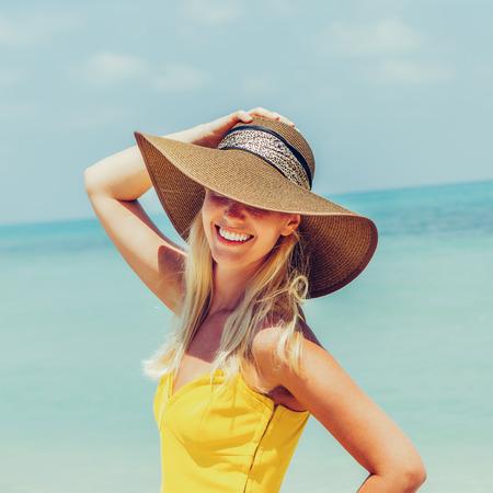 Sorgloses schönes Modeblondes Mädchen in Strandstrohhut und langem gelbem Kleid, das im Wind an der tropischen Strandküste fliegt. Natürliche Frauenschönheit. Dame hält ihren Hut und lächelt in die Kamera.
