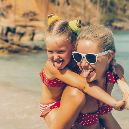 Beautiful mammy sunglasses with cute little daughter on her back. Two in red bikini. Woman and little lady show tongue and smile. Happy family on the shore. Happy mothers day.