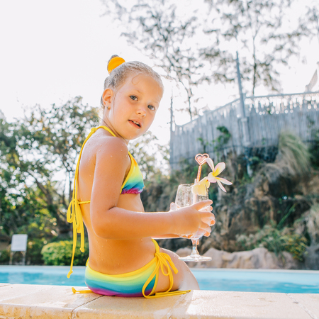Cute little blonde girl swimming in big pool. She sit on the pool edge. Little lady hold big glass with water, straw and frangipani and look to the camera. Sunbathing and leisure on sunny summer day.