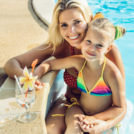 Outdoor portrait of beautiful blonde woman mother in bikini and her cute daughter in swimsuit. Little girl and her mammy look to the camera and smile. Happy family at the pool. Happy Mothers day. Stock Photo