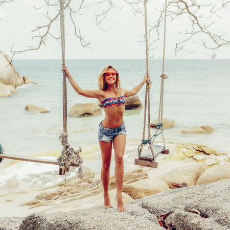 Beautiful girl in bikini, shorts and transparent cap near swings, she hold ropes and smile to camera. Summer holidays, vacation on a tropical island, sea and hot sand. Portrait of a sexy young lady.