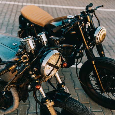 Two vintage custom motorcycle caferacer motorbike one with grill headlight another with tape cross over optic on empty rooftop parking lot during sunset. Hipster lifestyle. Lamp lights turned on. Imagens