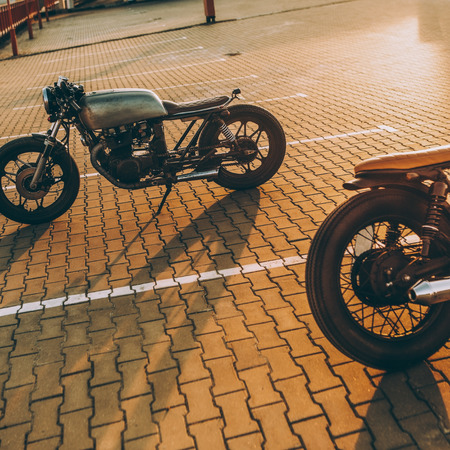Two vintage custom motorcycle cafe racer silver and black motorbikes directed in opposite directions on empty rooftop parking lot during sunset. Hipster lifestyle. Confrontation of urban styles.