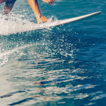 Close up of beautiful young Sporty girl in a bikini swimsuit ride big wave with lot of splashes. Sporty surfer woman surfing in Mauritius in the Indian Ocean on the transparent waves. Active Lifestyle