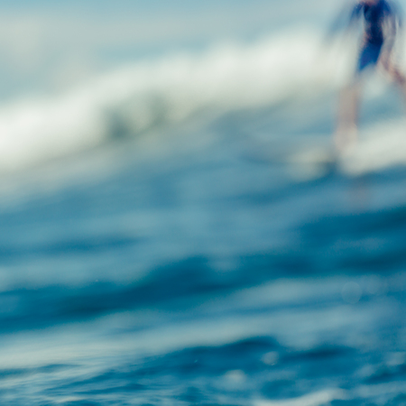Out of focus, blurred image. Beautiful young sporty girl in a bikini swimsuit ride big wave with lot of splashes. Fit surfer woman surfing in Mauritius in the Indian Ocean. Outdoor Active Lifestyle.