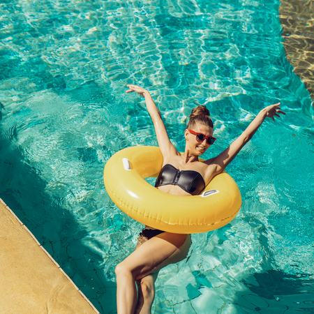 Happy beautiful woman in trendy swimsuit and sunglasses have fun in hotel swimming pool party. Young girl enjoying holiday, having fun and sunbathing on inflatable yellow ring in cool water. Foto de archivo