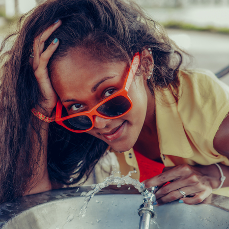 Outdoor lifestyle close-up of black sexy woman in bright sunglasses. Young thirsty hipster lady drinking water from a fixed water fountain station. She is happy. Sunny summer hot day. Swag, fashion.