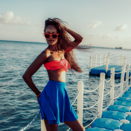 Beautiful sporty black girl in bright outfit and sunglasses at plastic pier at tropical seashore. Outdoor lifestyle portrait of female touch her long curly hair. Sunny hot summer day. Swag, fashion.