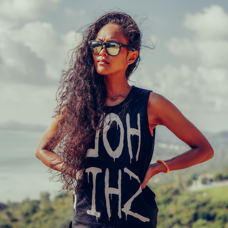 Outdoor portrait of a beautiful teenage black girl with curly hair in sunglasses and dark t-shirt. Lifestyle portrait with blue sky at background. Freedom and happiness.