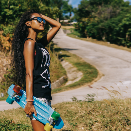 Outdoor lifestyle portrait of black beautiful teenage girl with her penny longboard skateboard. Woman correct her curly hair in front of danger mountain road. Freedom, challenge, doubt and happiness. Reklamní fotografie - 124702488