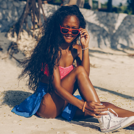 Outdoor lifestyle portrait of black beautiful teenage girl in bright outfit. Young hipster woman untying laces in her white converse sneakers. Sunny hot summer day at tropical ocean beach with palms.