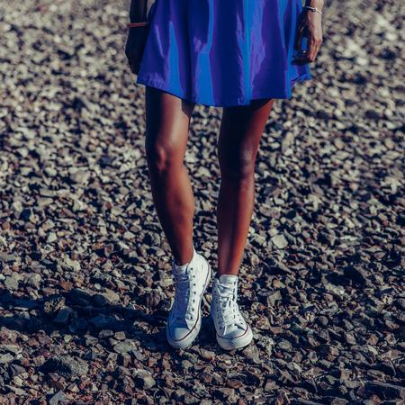 Gros plan sur un mode de vie en plein air sur de longues jambes sportives d'une dame noire en jupe bleue et baskets Converse blanches. Fille hipster bronzée se tenir à la plage de pierres de roche. Journée de vacances d'été chaude et ensoleillée. Style.