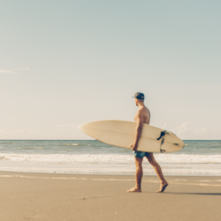 Out of focus, blurry image of handsome man walk with surfing board to surf spot at sea shore. View from side. Concept of sport, fitness, freedom, happiness, new modern life, hipster, generation Y.
