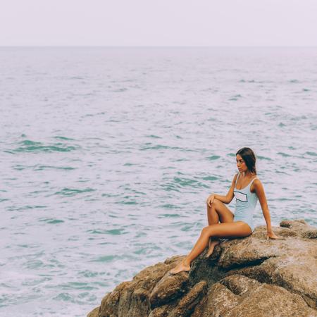 Chica guapa en traje de baño de cuerpo entero con largos pelos sanos se sienta en una piedra grande en la playa de rocas durante la tormenta de mar y toca su rodilla. Grandes olas cerca de sus piernas. Concepto de peligro, tristeza, malas emociones.