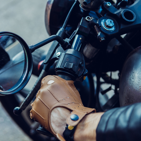 Close up of a hipster biker guy hand in leather glove hold throttle control of classic style cafe racer motorcycle. Bike custom made in vintage garage. Brutal fun urban lifestyle. Outdoor portrait.