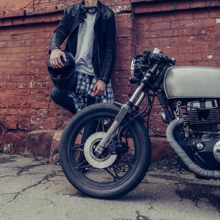 Close up of a handsome rider biker guy hand with black helmet near brick wall and classic style cafe racer motorcycle. Bike custom made in vintage garage. Brutal fun urban lifestyle. Outdoor portrait.