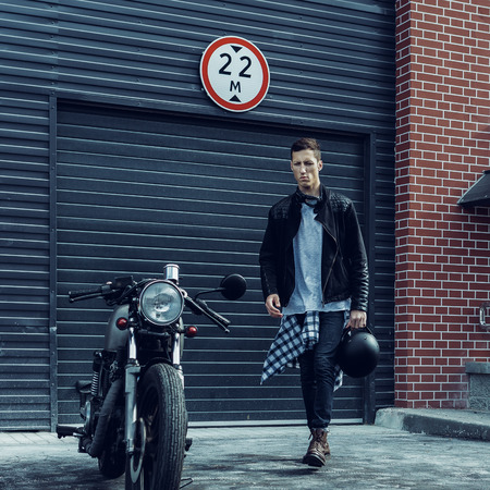 Handsome young rider guy in black biker jacket and denim go to his classic style cafe racer motorcycle industrial gates as background. Bike custom made in vintage garage. Brutal fun urban lifestyle.