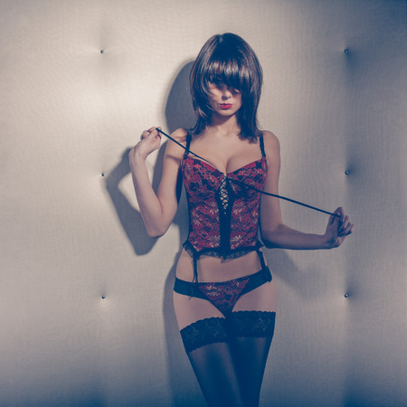 Seductive woman in a corset and stockings standing in front of white wall Banco de Imagens