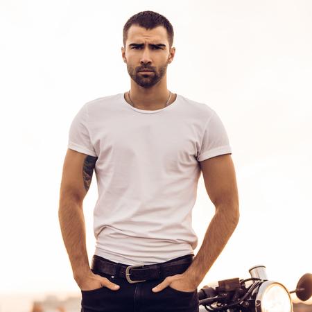 Nahaufnahme eines gutaussehenden Fahrermannes in weißem, leerem T-Shirt, Blick auf die Kamera in der Nähe des klassischen Café-Racer-Motorrads bei Sonnenuntergang. Fahrrad nach Maß in Vintage-Garage. Brutaler urbaner Lebensstil. Outdoor-Porträt.