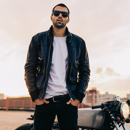 Handsome rider man with beard and mustache in black biker jacket, white t-shirt and fashion sunglasses smoking cigaret near classic style cafe racer motorbike at sunset. Brutal fun urban lifestyle. Stok Fotoğraf