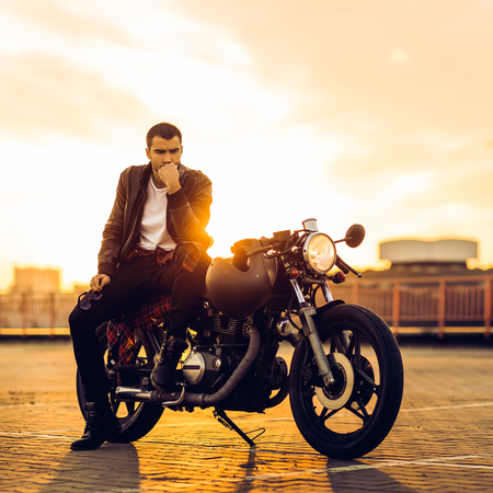 Handsome fit rider guy with beard and mustache in black leather biker jacket sit on classic style cafe racer motorcycle at sunset time. Bike custom made in vintage garage. Brutal fun urban lifestyle.