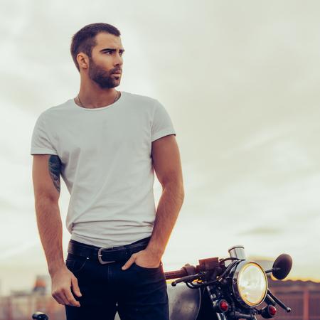 Motociclista sportivo bel pilota maschio in t-shirt bianca bianca a piedi dalla motocicletta cafe racer in stile classico al tramonto. Moto d'epoca realizzata su misura in garage. Stile di vita urbano brutale. Ritratto all'aperto.