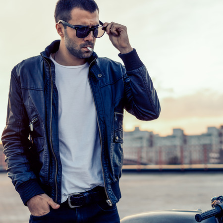 Close up of a handsome rider guy with beard and mustache in black biker jacket and sunglasses smoking cigaret near classic style cafe racer motorbike on rooftop at sunset. Brutal fun urban lifestyle.