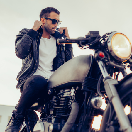 Handsome young rider man with beard and mustache in black fashion sunglasses smoking cigaret and correct biker jacket sit on classic style cafe racer motorbike at sunset. Brutal fun urban lifestyle.