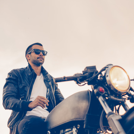 Handsome rider male with beard and mustache in black biker jacket, white shirt and fashion sunglasses smoke cigaret and sit on classic style cafe racer motorbike at sunset. Brutal fun urban lifestyle. Stok Fotoğraf