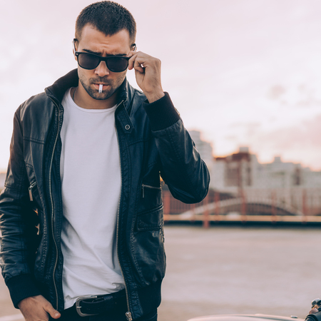 Closeup of a handsome rider man with beard and mustache in black biker jacket take off fashion sunglasses smoking cigaret near classic style cafe racer motorbike at sunset. Brutal fun urban lifestyle. Stok Fotoğraf
